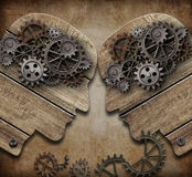 Two wooden heads with gears coming into collision concept stock photo