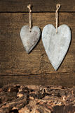 Two wooden hearts with bark on wooden background Royalty Free Stock Photography