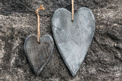 Two wooden hearts in front of stony background Royalty Free Stock Image