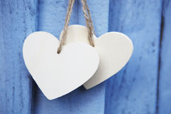 Two Wooden Hearts Hanging On Blue Wooden Surface Stock Image