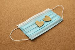 Two wooden hearts on a medical face mask