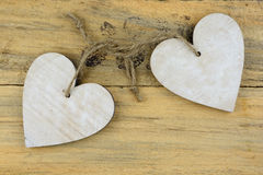 Two wooden hearts with on old wood holding with rope Royalty Free Stock Image