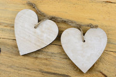 Two wooden hearts with on old wood holding with rope Stock Images