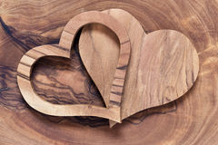 Two wooden hearts on a olive wood board Stock Image