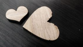 Two wooden hearts placed nicely on a turquoise vintage wood background Royalty Free Stock Images