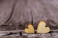 Two wooden hearts placed nicely on a vintage wood background. Copy space, love concept. stock photos