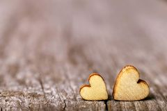 Two wooden hearts placed nicely on a vintage wood background. Copy space, love concept stock photography