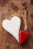 Two wooden hearts, red and white on old wood Stock Photos