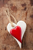 Two wooden hearts, red and white on old wood Royalty Free Stock Image