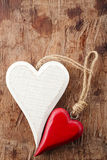 Two wooden hearts, red and white on old wooden background Royalty Free Stock Image