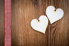 Two wooden hearts on sun burned wood. Plank with ribbon Stock Photo