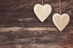 Two wooden hearts on wooden background. Copy space, soft focus, toned, vintage style Stock Images