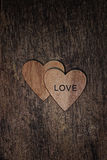 Two wooden hearts with word love on wood textured background Stock Photos