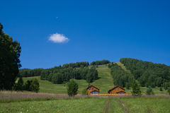 Two Wooden Hotels Near Hill In Summer Stock Photo