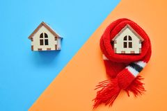 Two wooden house on blue and orange color, one house weared on scarf, concept for insulation houses divided diagonally royalty free stock images