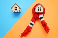 Two wooden houses on blue and orange background, one house weared on scarf, concept for insulation houses stock photos