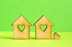 Two wooden houses with hole in the form of heart with little hea. Rt on green background Royalty Free Stock Images