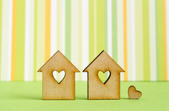 Two wooden houses with hole in the form of heart with little hea. Rt on green striped background Royalty Free Stock Photography