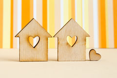 Two wooden houses with hole in the form of heart with little hea. Rt on orange striped background Stock Photography