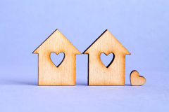 Two wooden houses with hole in the form of heart with little hea. Rt on purple background Stock Photography