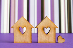 Two wooden houses with hole in the form of heart with little hea. Rt on purple striped background Stock Photo