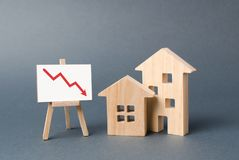Two wooden houses and a poster with a symbol of falling value. concept of real estate value decrease. low liquidity. And attractiveness of assets. cheapening royalty free stock image