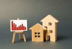 Two wooden houses with a stand with negative red trend chart. concept of real estate value decrease. low liquidity. And attractiveness. cheap rent or cost of stock photography