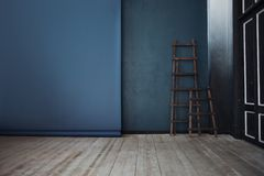 Two Wooden ladder, near dark blue wall, perspective Royalty Free Stock Images