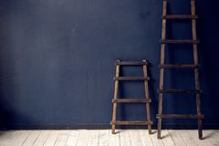 Two wooden ladders stand at the blue wall on white floor Stock Images