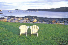 Two wooden lawn chairs set near the shore with a view of the harbor in the lobster village of Tenants Harbor, ME Royalty Free Stock Photos