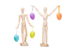 Two wooden little men with easter eggs on isolated white Royalty Free Stock Photos