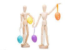 Two wooden little men with easter eggs on isolated white Stock Image
