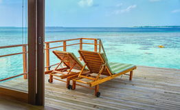 Two wooden lounge chairs on the deck of water bungalow suite overlooking the lagoon and sea horizon in Maldives Stock Photo