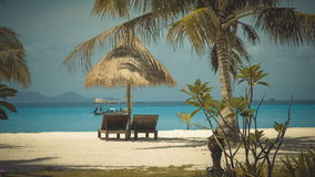 Two wooden lounge chairs under palm tent on beach. Longtail on background in ocean, Ko Lipe, Thailand stock footage