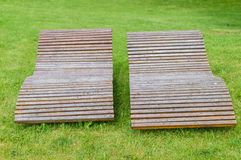 Two wooden lounge sunbeds standing on green grass. In park Royalty Free Stock Photo