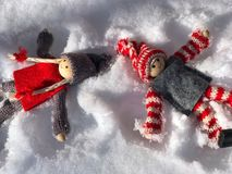 Two wooden man girl and a boy lying in the snow Stock Photography