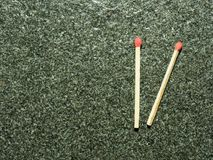 Two wooden match sticks with red head over black or dark granite texture. With concepts of energy, old fashion, vintage, and retro Stock Photography