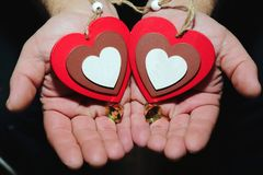 Two wooden multicolored hearts in male hands on the palms - a sy. Mbol of love and mercy Stock Photography