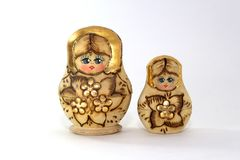 Two wooden nested dolls on a white background close-up. Two Russian wooden nested dolls on a white background close-up Royalty Free Stock Photo