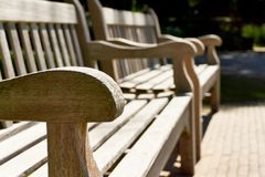 Two wooden park benches in the sun. Close-up of two wooden classic teak park benches in the sun in summer with selective focus on one armrest Royalty Free Stock Images
