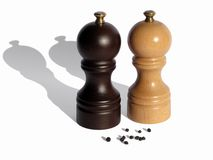 Two wooden pepper mills. With peppercorns isolated on white background Stock Image
