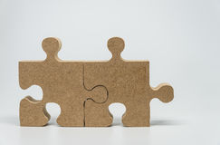 Two Wooden pieces of jigsaw puzzle with white background and selelective focus Royalty Free Stock Photography