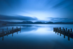 Two Wooden pier or jetty and on a blue lake sunset and sky refle Stock Photo