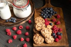 Two wooden platters with chcocolate biscuits, raspberries, blueberries, milk and flour. stock photos