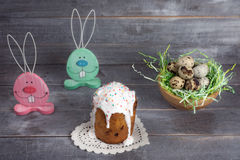 Two wooden rabbit, a nest with quail eggs and Easter cakes with Royalty Free Stock Photography