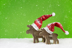 Two wooden reindeer: funny green and white christmas background. Stock Photo