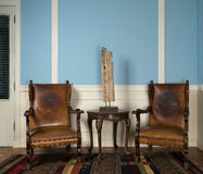 Two wooden retro armchairs, table lamp and round coffee table Stock Photography
