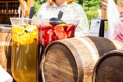 Large glass containers with red and yellow drinks and a wooden barrel with homemade wine royalty free stock images