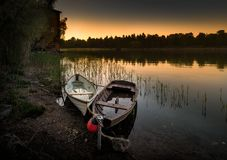 Wooden rowboats on the sunset. Two Wooden rowboats on a nordic sunset Royalty Free Stock Images