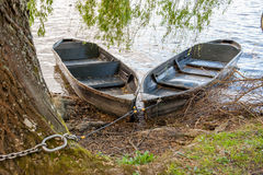 Two wooden rowing boats. Tied to tree on river bank Stock Images